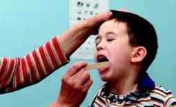 γιατρός εξετάζει το λαιμό παιδιού