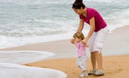 μαμά με το μωρό στην αμμουδιά