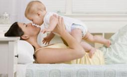 μαμά και μωρό παίζουν στο κρεβάτι