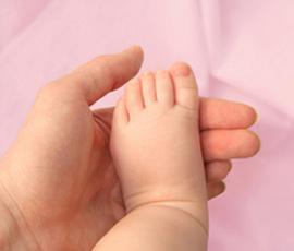πατέρας κρατάει πόδι νεογέννητου