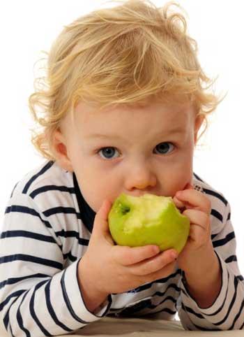 μωρό τρώει πράσινο μήλο